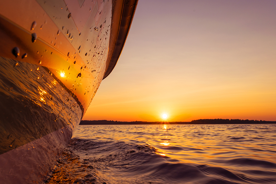 the side of a boat facing the sunset